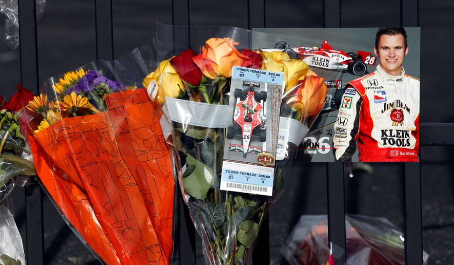 Fans created a memorial at the main gate at Indianapolis Motor Speedway for driver Dan Wheldon, who was killed in a crash during an IndyCar race at Las Vegas on Oct. 16. The incident spurred the racing organization to enhance safety measures in advance of the 2012 season. (Associated Press)