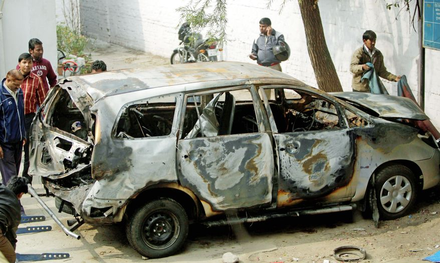 Indian police officers check out an Israeli diplomat's car that was damaged in an explosion Tuesday in New Delhi. Indian investigators suspect that a motorcycle rider attached the bomb to the car. (Associated Press)