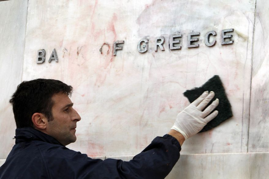 A worker cleans the sign of the Bank of Greece from red and black paint, after Sunday's riots, in Athens, on Tuesday, Feb. 14, 2012. (AP Photo/Thanassis Stavrakis)