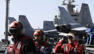 Crew members keep watch over the Arabian Sea from the flight deck of the Nimitz-class aircraft carrier USS Abraham Lincoln as the ship transits the Strait of Hormuz on Tuesday, Feb. 14, 2012. (AP Photo/Hassan Ammar)