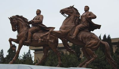 A new bronze statue depicting the late North Korean leader Kim Jong-il (right) and his father, Kim Il-sung, stands on the grounds of the Mansudae Art Studio after it was unveiled in Pyongyang, North Korea, on Tuesday, Feb. 14, 2012. (AP Photo/David Guttenfelder)
