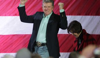 "Idaho Gov. C.L. ""Butch"" Otter reacts to the crowd as he and his wife Lori, right, take the stage for a rally with Republican presidential candidate, former Massachusetts Gov. Mitt Romney, Friday, Feb. 3, 2012, in Elko, Nev. (AP Photo/Ted S. Warren)"