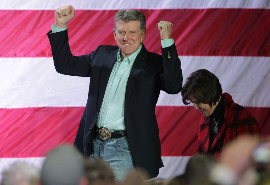 """Idaho Gov. C.L. """"Butch"""" Otter reacts to the crowd as he and his wife Lori, right, take the stage for a rally with Republican presidential candidate, former Massachusetts Gov. Mitt Romney, Friday, Feb. 3, 2012, in Elko, Nev. (AP Photo/Ted S. Warren)"""
