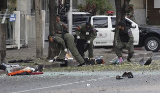 Thai explosive ordnance disposal officers examine the site in Bangkok at which an Iranian man carrying grenades blew off his own legs and wounded four civilians on Tuesday, Feb. 14, 2012. (AP Photo/Apichart Weerawong)