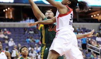 **FILE** Victoria Dunlap (right) of the Washington Mystics goes to the basket against the Seattle Storm's Le'coe Willingham during the Storm's 73-63 home win on July 3, 2011. (Associated Press)
