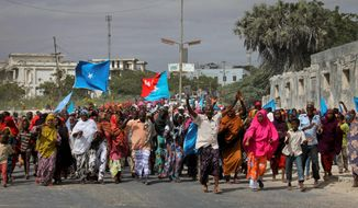 Somalis march through the streets of Mogadishu at a government-organized rally against the militant group al-Shabab on Wednesday. Many of the demonstrators were protesting the recent merger between al Qaeda and al-Shabab. (Associated Press)