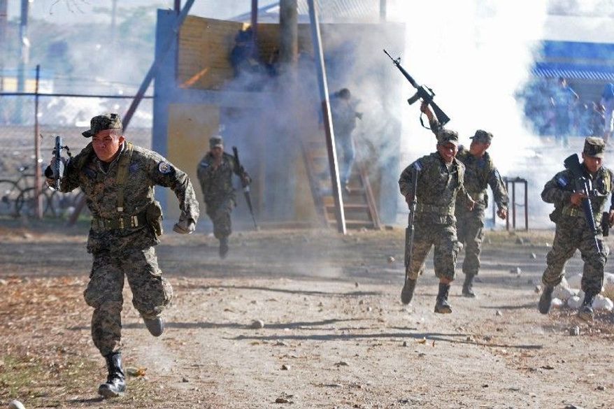 ASSOCIATED PRESS PHOTOGRAPHS Soldiers scramble during clashes Wednesday with relatives of inmates after a deadly prison fire in Comayagua, Honduras. As many as 350 inmates are missing and presumed dead and at least 21were injured in the blaze, authorities said.