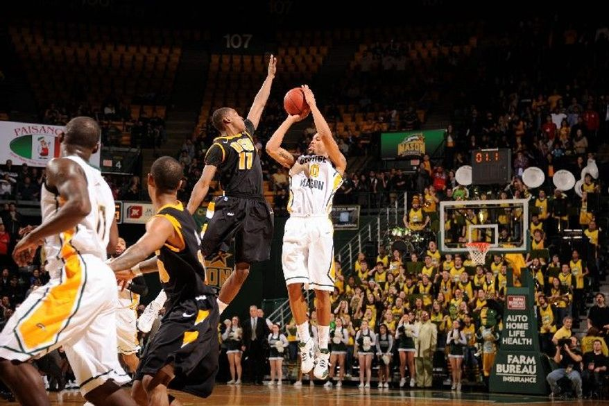 """George Mason guard Sherrod Wright takes the game-winning shot over Virginia Commonwealth's Rob Brandenberg as time expires in a 62-61 triumph Tuesday at the Patriot Center. """"Everybody dreams of making a big-time shot to get a big win against your rivals,"""" Wright said. """"My dream came true today."""" (George Mason Athletics)"""