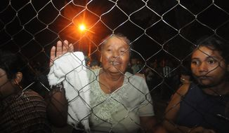 Inmates' relatives stand at the gates of the prison in Comayagua, Honduras, early on Wednesday, Feb. 15, 2012,  after a fire broke out inside the facility Tuesday night. (AP Photo/Fernando Antonio)