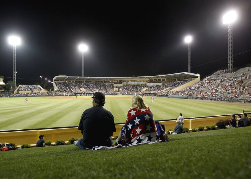 In this March 24, 2011 photo, fans take in a spring training baseball game between the Washington Nationals and Detroit Tigers in Lakeland, Fla. (AP Photo/David Goldman)