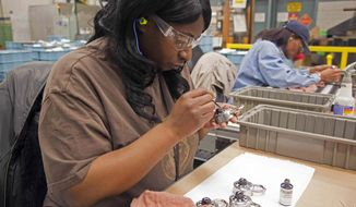 ** FILE ** In this Jan. 25, 2012, file photo Delisa Scales touches up locks inside Master Lock in Milwaukee, Wis. President Barack Obama will try to use his visit to Master Lock Wednesday, Feb. 15, 2012, to show how the economy is improving and companies are growing jobs in the United States instead of shipping them overseas, but the success story hasn't translated across Wisconsin, which has lost private sector jobs each of the past six months. (AP Photo/Jeffrey Phelps, File)