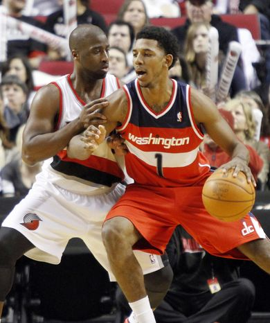 Washington Wizards guard Nick Young, right, drives on Portland Trail Blazers guard Raymond Felton during the second half of their NBA basketball game in Portland, Ore., Tuesday, Feb. 14, 2012. Young sank seven of eight three-point shots while scoring 35 points to lead the Wizards to a 124-109 win over the Blazers. (AP Photo/Don Ryan)