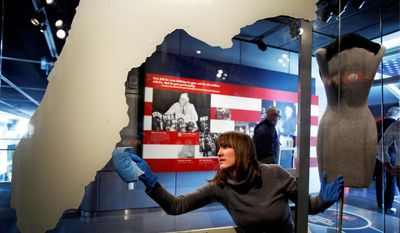 Emma Krebs, a collections technician with the Newseum, dusts a map of Florida, which played a pivotal role in the 2000 election. (Associated Press)