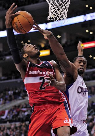 Los Angeles Clippers center DeAndre Jordan, right, blocks the shot of Washington Wizards point guard John Wall during the first half Wednesday, Feb. 15, 2012, in Los Angeles. (AP Photo/Mark J. Terrill)
