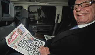 News Corp. chief executive Rupert Murdoch reads his group's the Sun daily newspaper on Feb. 17, 2012, as he is driven from his home in central London. (Associated Press)