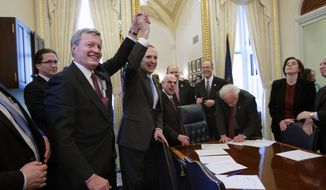 Senate Finance Committee Chairman Sen. Max Baucus (left), Montana Democrat, and House Ways and Means Committee Charman Rep. David Camp, Michigan Republican, raise their hands Feb. 16, 2012, on Capitol Hill as the bipartisan House and Senate conferees gather to sign the compromise agreement. (Associated Press)