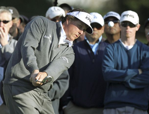 Phil Mickelson chips from the gallery to the 12th green during the second round of the Northern Trust Open golf tournament at Riviera Country Club in Los Angeles Friday, Feb. 17, 2012. (AP Photo/Reed Saxon)