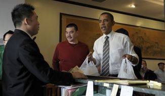President Obama greets the crowd Feb. 16, 2012, as he waits for his Chinese food from Great Eastern Restaurant in San Francisco. (Associated Press)