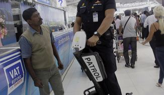 An Airport Security officer talks Feb. 17, 2012, to a tourist during a patrol at Suvarnabhumi airport in Bangkok. Thai police said they are searching for two more suspects, including a possible explosives specialist, in a botched terror plot against Israeli diplomats that has been blamed on Iran. (Associated Press)