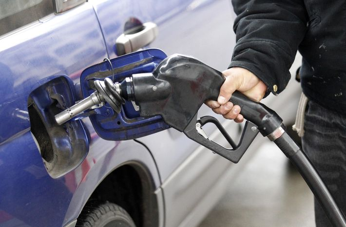 A service station attendant pumps gas in Portland, Ore., in February 2012. (AP Photo/Rick Bowmer)