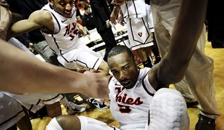 Teammates swarm Virginia Tech's Dorenzo Hudson after he hit the game-winning 3-pointer as time expired in overtime against Georgia Tech, Saturday, Feb. 18, 2012, in Blacksburg, Va. Virginia Tech won 74-73. (AP Photo/The Roanoke Times, Kyle Green)