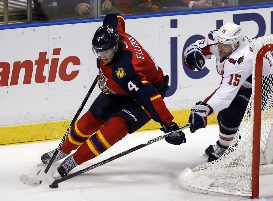 Washington Capitals' Jeff Halpern (15) reaches for the puck as Florida Panthers' Keaton Ellerby (4) drives in the second period of an NHL hockey game in Sunrise, Fla., Friday, Feb. 17, 2012. (AP Photo/Alan Diaz)