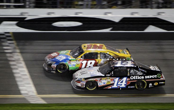 Kyle Busch (18) beats Tony Stewart (14) to the finish line to win the NASCAR Budweiser Shootout auto race at Daytona International Speedway, Saturday, Feb. 18, 2012, in Daytona Beach, Fla. (AP Photo/John Raoux)