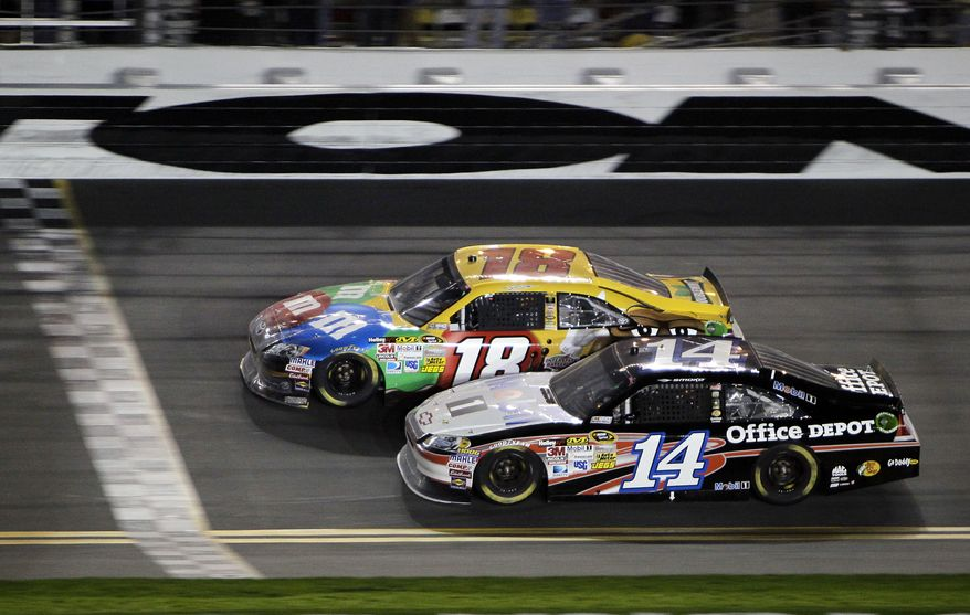 Kyle Busch (18) beats Tony Stewart (14) to the finish line to win the NASCAR Budweiser Shootout auto race at Daytona International Speedway, Saturday, Feb. 18, 2012, in Daytona Beach, Fla. (AP Photo/John Raoux)