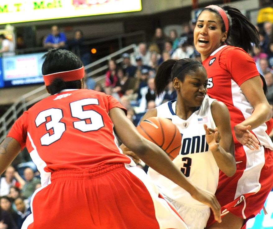 Connecticut's Tiffany Hayes pushes past St. John's Shenneika Smith, left, and Mary Nwachukwu for a shot in the first half in Storrs, Conn., Saturday, Feb. 18, 2012. (AP Photo/Bob Child)