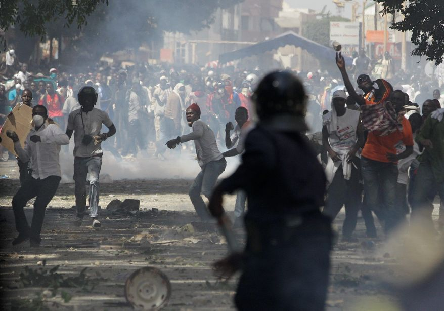 Protesters throw rocks at police, who respond with tear gas, on a central boulevard in Dakar, Senegal, on Sunday. The fifth consecutive day of pre-election clashes took on a religious dimension in this normally tolerant Muslim nation. (Associated Press)