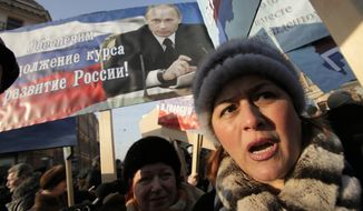"""Demonstrators in St. Petersburg on Saturday, Feb. 18, 2012, hold a poster depicting Russian Prime Minister Vladimir Putin during a rally in support of Mr. Putin's candidacy for the presidency in the March 4 elections. The sign reads: """"Will provide continuation of Russia's development!"""" (AP Photo/Dmitry Lovetsky)"""