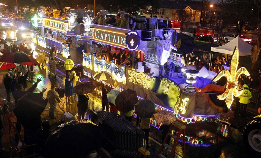"""A float dubbed """"Flingin' in the Rain"""" rolls down Orleans Avenue under rainy skies on Saturday in New Orleans. The annual Mardi Gras celebration gives a financial boost to the city and to the builders and artists who work on parade floats. (Associated Press)"""