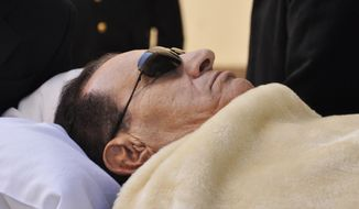 **FILE** Former Egyptian president Hosni Mubarak is wheeled into a courthouse on Jan. 22 2012, in Cairo. Mubarak, who stepped down nearly a year ago, is charged along with his security chief and four police commanders of complicity in the killing of protesters during an 18-day uprising. (Associated Press)