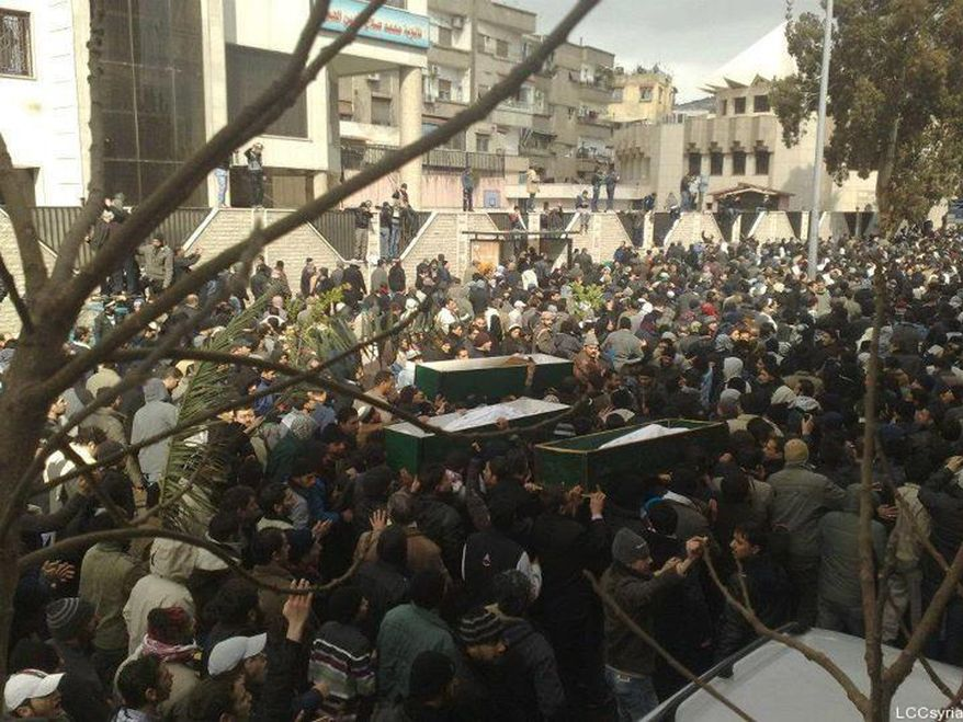 In this citizen journalism image provided by the Local Coordination Committees in Syria, anti-Syrian regime mourners carry Feb. 18, 2012, the coffins of three protesters that, according to Syrian activists, were killed by the Syrian security forces during a demonstration at Mazzeh district in Damascus. (Associated Press/Local Coordination Committees in Syria)