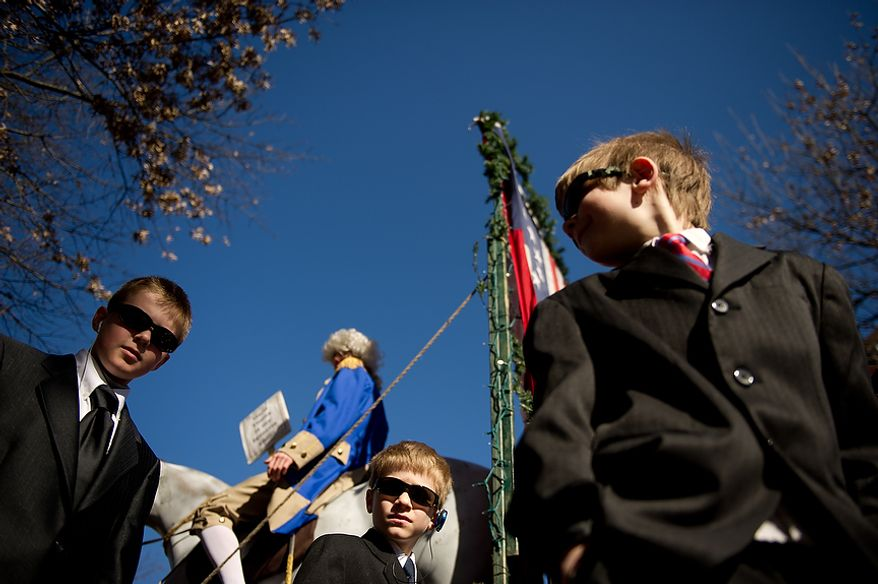 """Dane Kappeler, left, Owen Hull, 7, center, and Adrian Allred, 9, dress as secret service agents to protect George Washington, played by Ned Parker, second from left, as he sits on a parade float for Hard Times Cafe during the George Washington Birthday Parade in Old Town, Alexandria, Va., Monday, Feb. 20, 2012. The Parade which celebrates Washington's 280th Birthday is touted as being the """"largest parade celebrating Washington's birthday in the USA."""" (Andrew Harnik/The Washington Times)"""