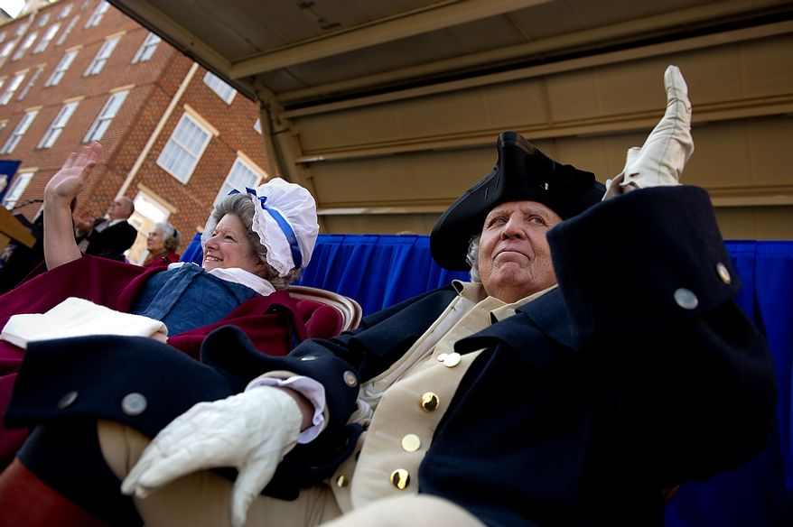 """George Washington, played by Donald De Haven, and Martha Washington, played by Kari La Bell, right, wave from the main parade stand during the George Washington Birthday Parade in Old Town, Alexandria, Va., Monday, Feb. 20, 2012. The Parade which celebrates Washington's 280th Birthday is touted as being the """"largest parade celebrating Washington's birthday in the USA."""" (Andrew Harnik/The Washington Times)"""