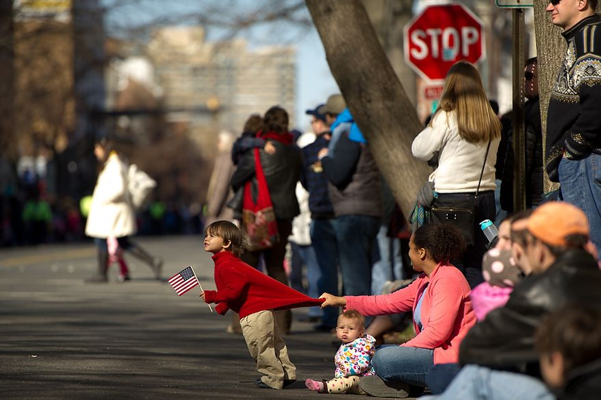 """Lisa Keyser of Old Town Alexandria, Va., keeps her son Adrian, 3, from running out into street as her 3 month old daughter Carmen sits quietly during the George Washington Birthday Parade in Old Town, Alexandria, VA, Monday, Feb. 20, 2012. The Parade which celebrates Washington's 280th Birthday is touted as being the """"largest parade celebrating Washington's birthday in the USA."""" (Andrew Harnik/The Washington Times)"""