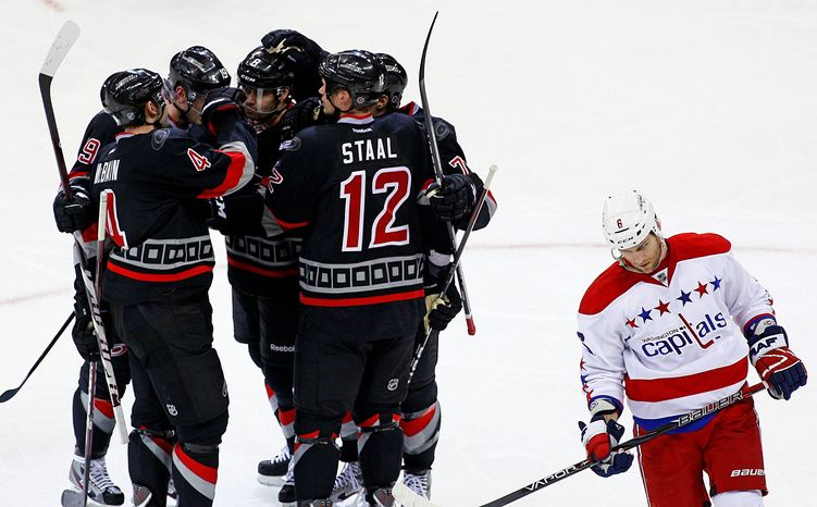 Carolina celebrates a goal by Eric Staal as Washington defenseman Dennis Wideman skates by. The Hurricanes routed the Capitals 5-0 on Monday night. (Associated Press)