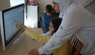 "Sarah Yazback helps her daughter Zainab find an arithmetic lecture video online. ""I am here for resources and help if necessary,"" Ms. Yazback says, ""but the kids are very independent and self-guided with their lessons."" (Jessica Carpenter/The Washington Times)"