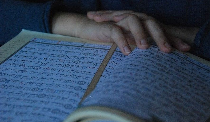 A child reads from the Koran at his home. (Associated Press) ** FILE **