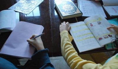Ahmad, 12, (left) and Zainab Bannout, 9, each have their own Arabic workbook, and after they finish their lesson, they read the Koran as part of their home-schooling in Montgomery County. They are home-schooled by their mother, who has a master's degree in education psychology,
