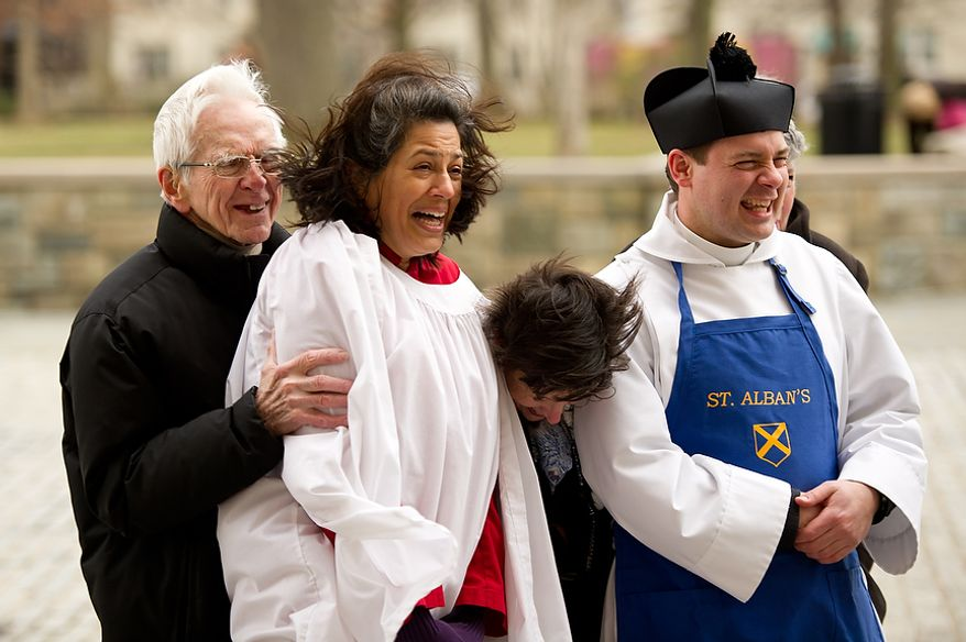 """Left to right: Head Volunteer Coordinator for St. Alban's David Johnson, Director of Music of St. Alban's and last years pancake race champion Sonya Sutton, Parish Coordinator for St. Alban's Annemarie Stroud, and Assistant Rector for St. Alban's Parish Reverend Matthew Hanisian react to cold winds before the start of the Washington National Cathedral Pancake Races held in front of the Cathedral on Shrove Tuesday, more commonly known as """"Mardi Gras."""", Washington, D.C., Tuesday, Feb. 21, 2012. This years annual Pancake Races are entitled the """"Shake, Rattle & Race Edition,†in light of the earthquake damage the cathedral sustained earlier this year. (Andrew Harnik/The Washington Times)"""