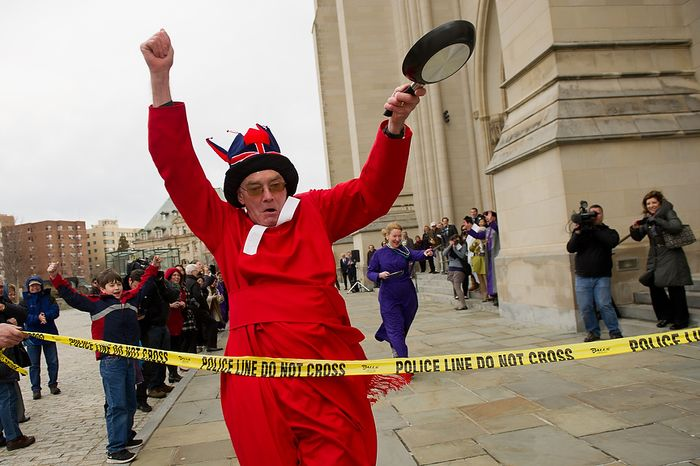 """The Rev. Canon Ralph Godsall, priest vicar of Westminster Abbey and visiting clergy at the Washington National Cathedral celebrates as he crosses the finish line during the National Cathedral Pancake Races held in front of the Cathedral on Shrove Tuesday, more commonly known as """"Mardi Gras."""", Washington, D.C., Tuesday, Feb. 21, 2012. This years annual Pancake Races are entitled the """"Shake, Rattle & Race Edition,†in light of the earthquake damage the cathedral sustained earlier this year. (Andrew Harnik/The Washington Times)"""