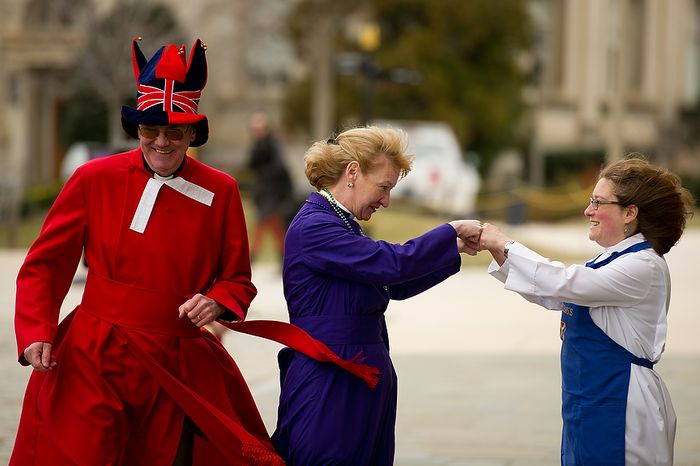 """The Rev. Canon Ralph Godsall, priest vicar of WestminsterAbbey and visiting clergy at the Cathedral gets ready to start his race along side the Rev. Canon Jan Naylor Cope, National Cathedral Vicar who fist bumps with the Rev. Deborah Meister, Rector of St. Alban's Parish during the Washington National Cathedral Pancake Races held in front of the Cathedral on Shrove Tuesday, more commonly known as """"Mardi Gras."""", Washington, D.C., Tuesday, Feb. 21, 2012. This years annual Pancake Races are entitled the """"Shake, Rattle & Race Edition,†in light of the earthquake damage the cathedral sustained earlier this year. (Andrew Harnik/The Washington Times)"""