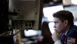 A trader works on the floor of the New York Stock Exchange on Tuesday, Feb. 21, 2012, in New York. (AP Photo/Seth Wenig)