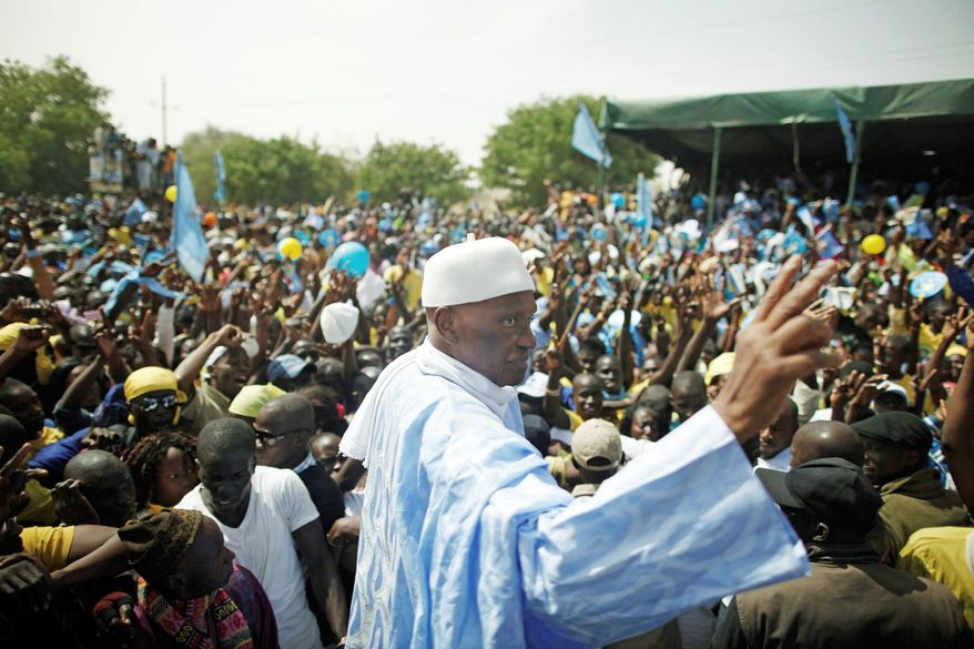 President Abdoulaye Wade waves to supporters at a campaign rally in his hometown of Kebemer, Senegal, on Feb. 9. As Mr. Wade tries to persuade voters to give him a third term on Sunday, his age has become a campaign issue. Officially, he was born on May 29, 1926, making him 85 years old. His critics contend that he may be 90. (Associated Press)