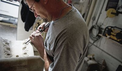 ANDREW HARNIK/THE WASHINGTON TIMES Mr. Uhl's repairs to a finial base require a steady hand. Stone carvers are just beginning to assess which pieces of the central tower's damaged pinnacles can be repaired and which need to be redone out of new pieces of Indiana limestone.