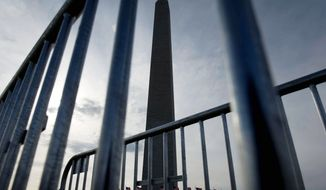 ROD LAMKEY JR/THE WASHINGTON TIMES The Washington Monument, seen through barricades on the Mall, remains closed since August's earthquake. Design for repairs should last into midspring, when bidding will begin. Work will be paid with $15 million in federal and private funding.