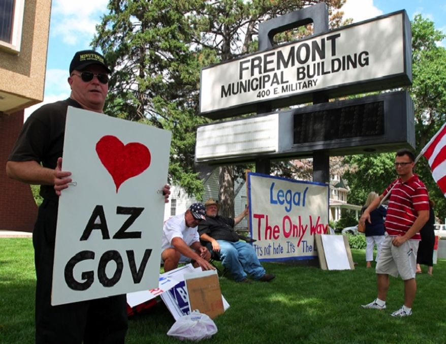 In this July 13, 2010, photo, Greg Casady of Council Bluffs, Iowa, holds a sign in favor of recent legislation in Arizona while demonstrating in support of recent legislation dealing with illegal immigration at the Fremont, Neb., Municipal Building. A federal judge on Monday, Feb. 20, 2012, rejected a portion of the city of Fremont's ordinance that would have denied housing permits to illegal immigrants, but upheld a requirement that employers verify the citizenship status of people they hire. (AP Photo/The Omaha World-Herald, Mark Davis)
