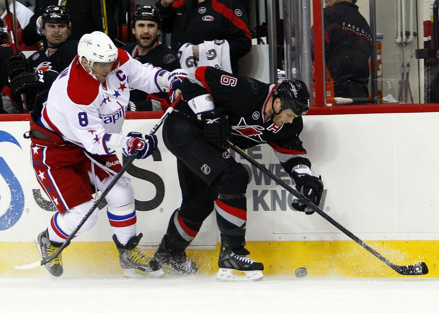 Washington Capitals' Alex Ovechkin (8) and Carolina Hurricanes' Tim Gleason (6) work along the boards during the first period in Raleigh, N.C., Monday, Feb. 20, 2012. (AP Photo/Karl B DeBlaker)